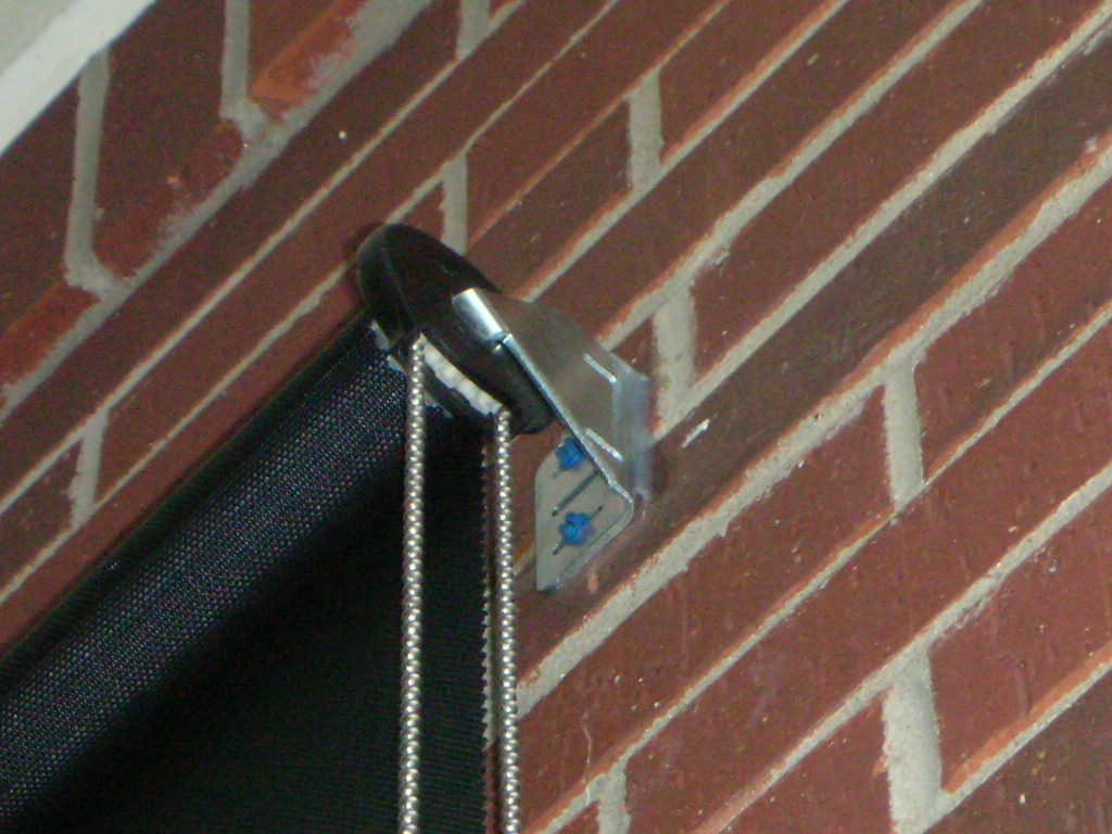 Clutch, bracket and tapcon screws for exterior patio roller shades mounted to shade a front door.