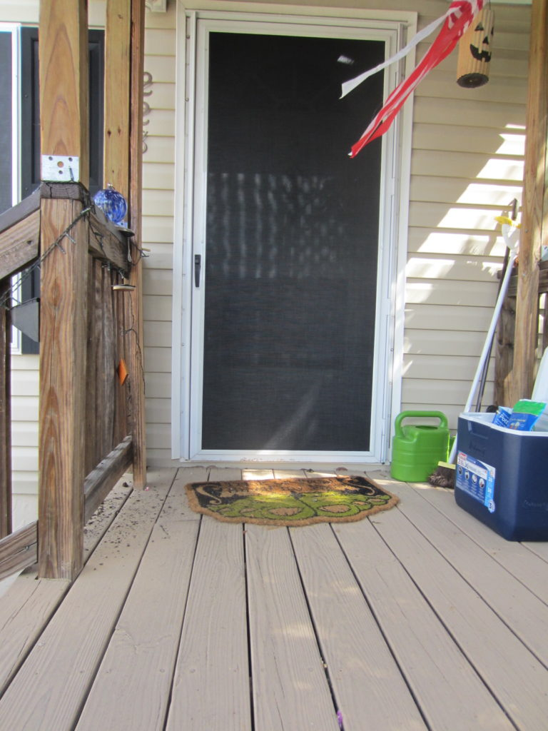 Storm door of a mobile home wearing a black 90% solar screen with white frame.