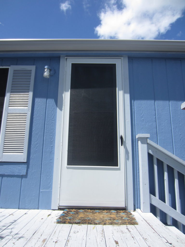 We used a black 90% fabric solar screen outlined with white framing for this mobile home storm door.