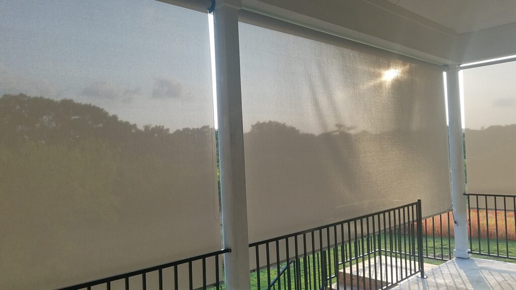 Retractable grey white patio roller shade.